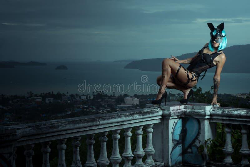 Mujer sensual en peluca azul con las correas de cuero y la máscara del conejo imagen de archivo