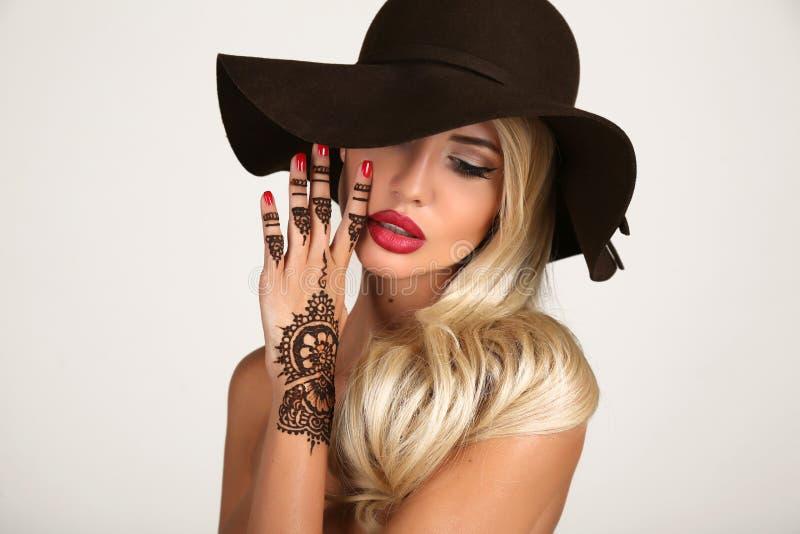 Mujer sensual en sombrero negro elegante con el tatuaje de la alheña en las manos imagen de archivo libre de regalías