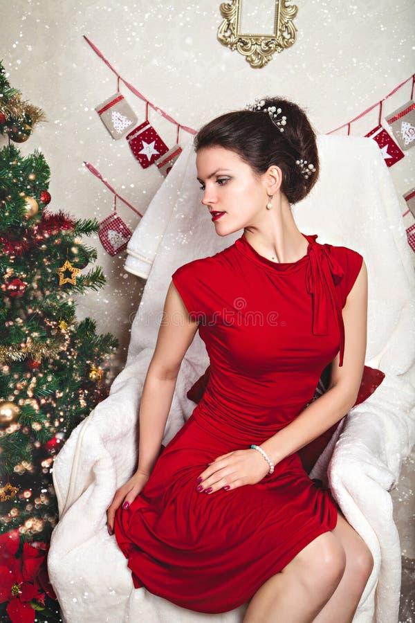 Mujer sensual en vestido rojo entre la decoración de la Navidad fotos de archivo libres de regalías