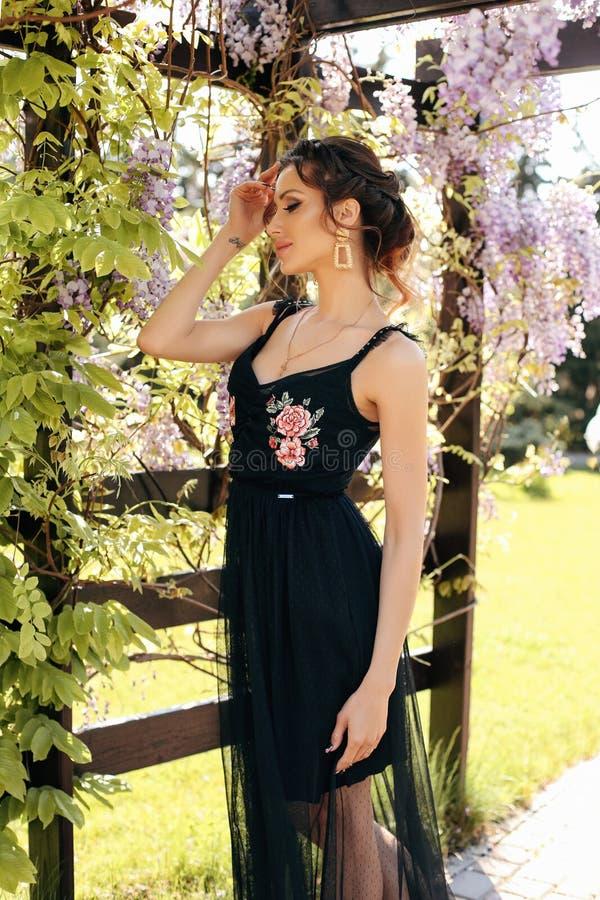 Mujer sensual hermosa con el pelo oscuro en la ropa elegante que presenta en jardín con los árboles de florecimiento de la glicin imagen de archivo libre de regalías