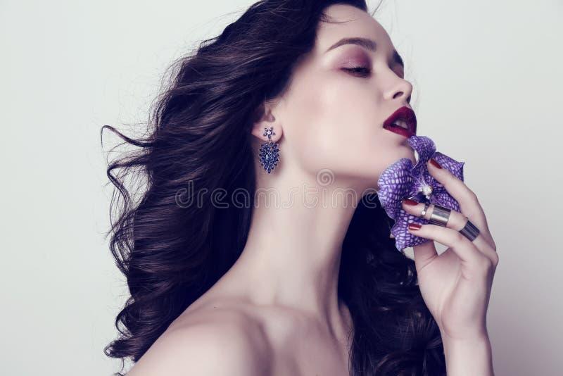 Mujer sensual hermosa con el pelo oscuro y maquillaje brillante con la joya fotografía de archivo