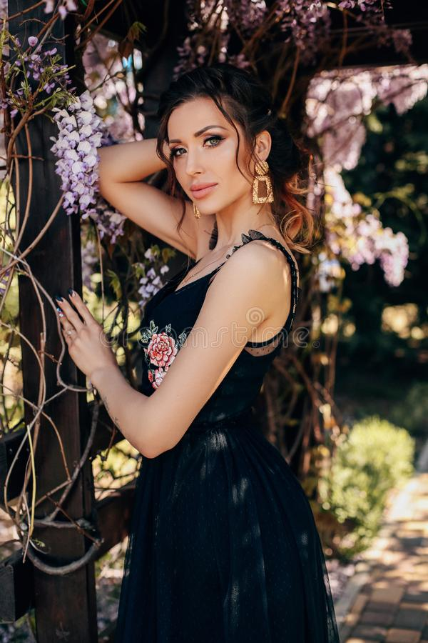 Mujer sensual hermosa con el pelo rubio en la ropa elegante que presenta en jardín con los árboles de florecimiento de la glicini fotos de archivo
