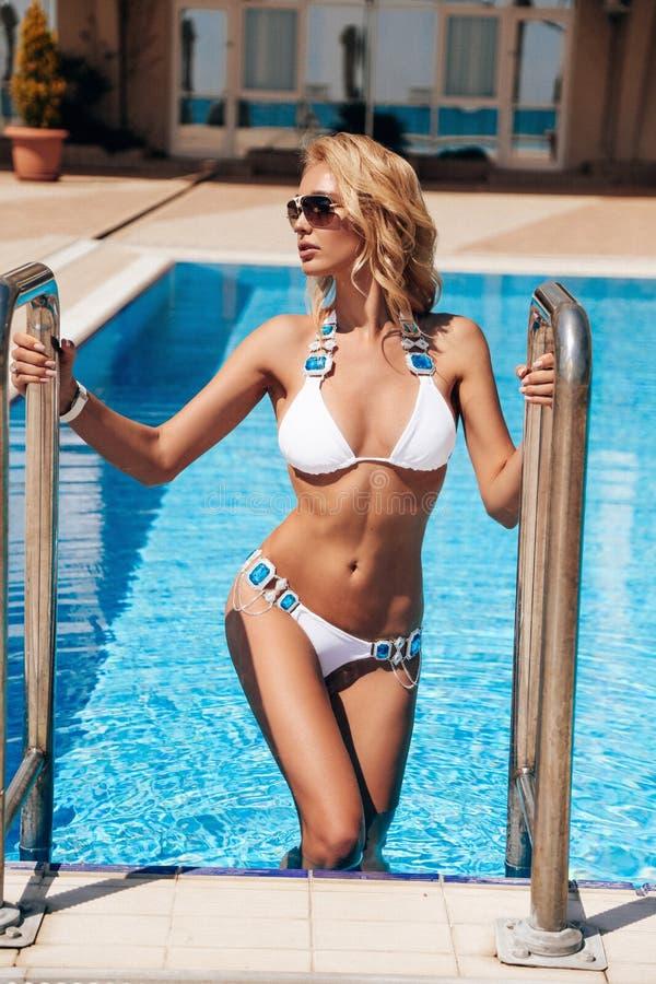 Mujer sensual hermosa con el pelo rubio en el traje que nada elegante que presenta cerca de piscina del aire abierto fotos de archivo