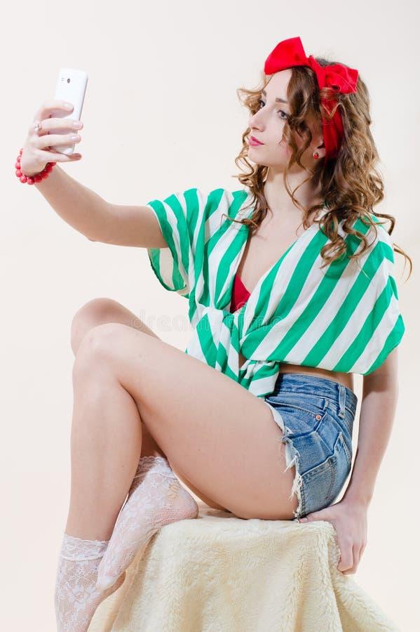 Mujer sensual hermosa de la muchacha atractiva modela que se sienta en una silla y que hace el selfie en el teléfono, fondo blanc imagenes de archivo