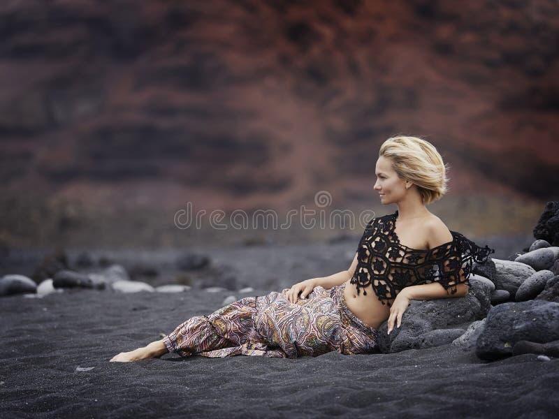 Mujer sensual joven que presenta en la playa volcánica en verano foto de archivo libre de regalías