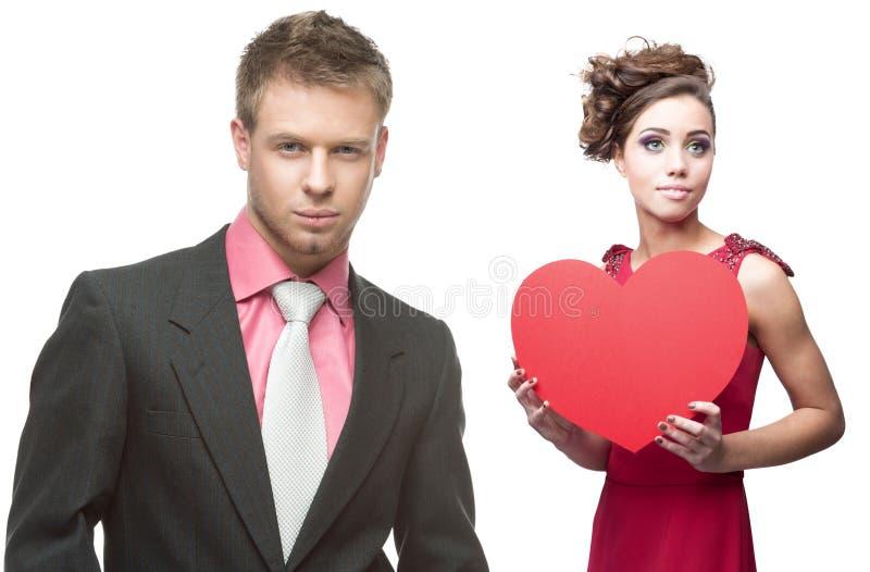 Mujer sensual joven y hombre hermoso que llevan a cabo el corazón rojo en blanco fotografía de archivo