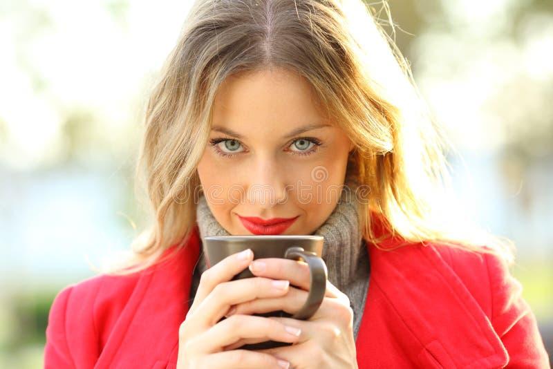 Mujer sensual que mira la cámara con la taza de café foto de archivo libre de regalías