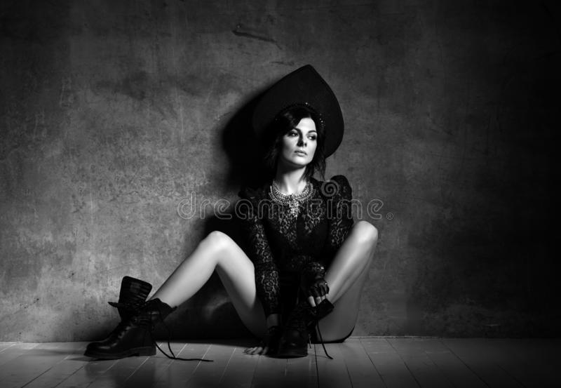 Mujer sensual y pensativa en ropa interior elegante de la ropa del neofolk y kokoshnik que se sienta en el muro de cemento en act imagenes de archivo