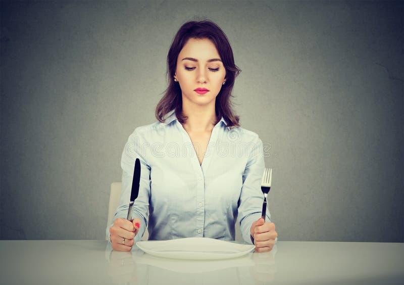 Mujer seria con la bifurcación y cuchillo que se sienta en la tabla con la placa vacía foto de archivo libre de regalías