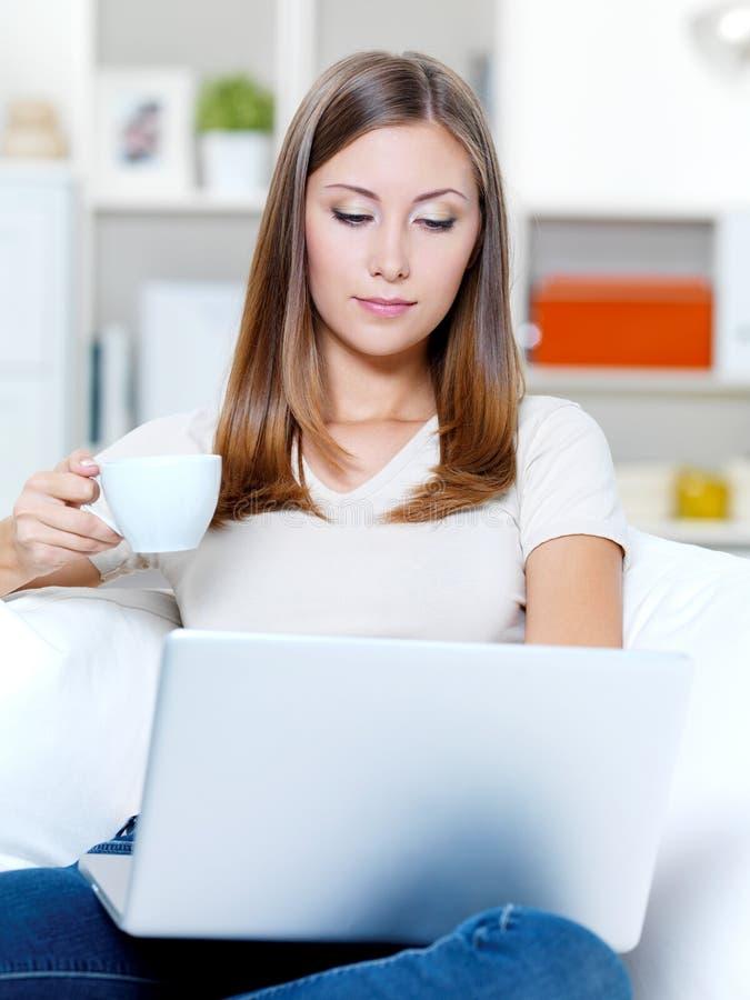 Mujer seria con la computadora portátil y la taza de café imágenes de archivo libres de regalías