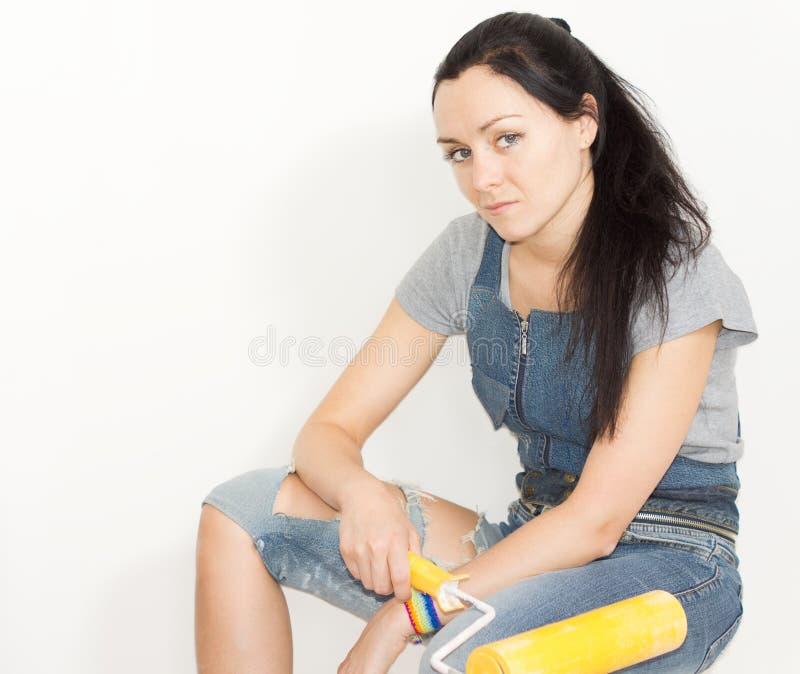 Mujer seria con un rodillo de pintura fotografía de archivo