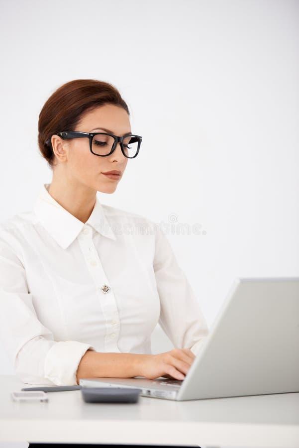Mujer seria de la oficina que mecanografía en el ordenador portátil imagen de archivo libre de regalías