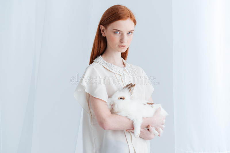 Mujer seria del pelirrojo que sostiene el conejo foto de archivo