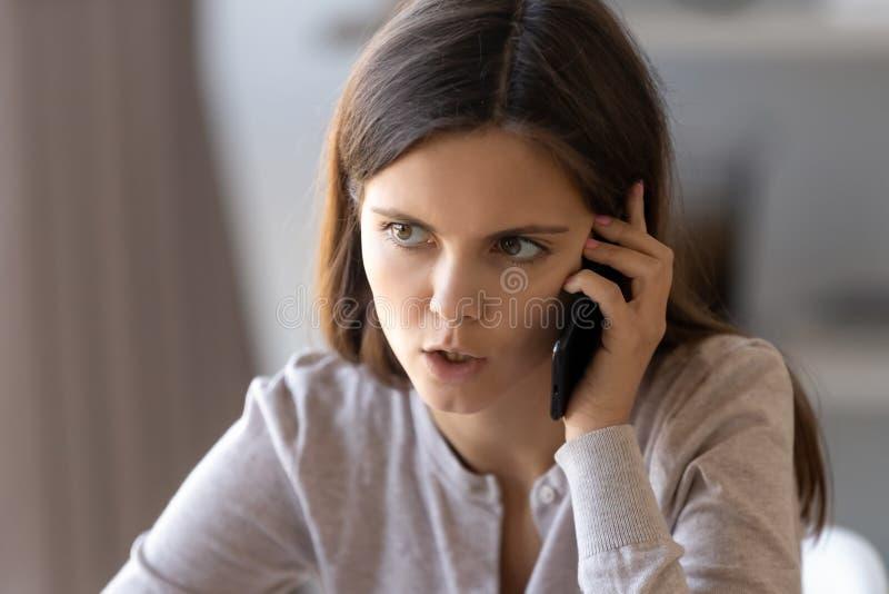 Mujer seria del retrato ascendente cercano que tiene conversación desagradable sobre el teléfono fotografía de archivo