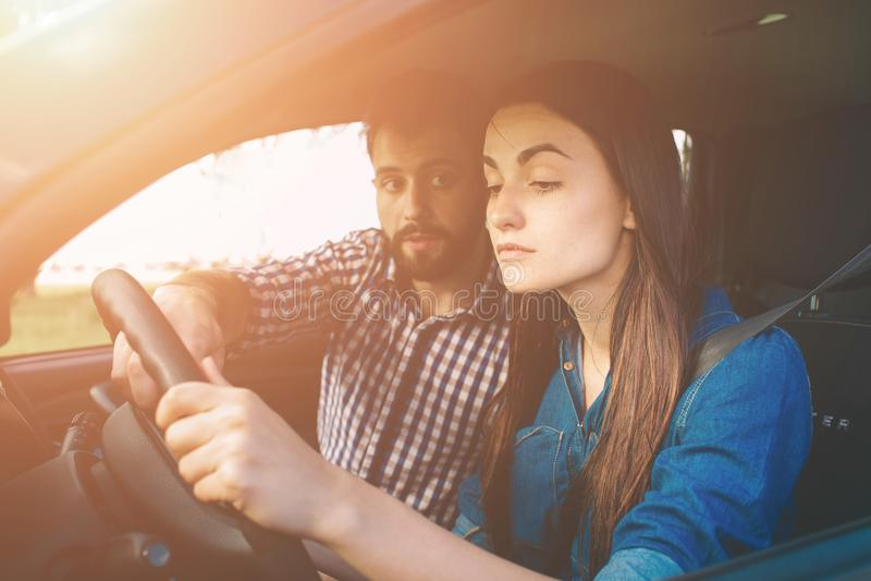 Mujer seria joven de la prueba de conducción que conduce el coche que siente inexperto, mirando nervioso el tráfico por carretera fotos de archivo libres de regalías