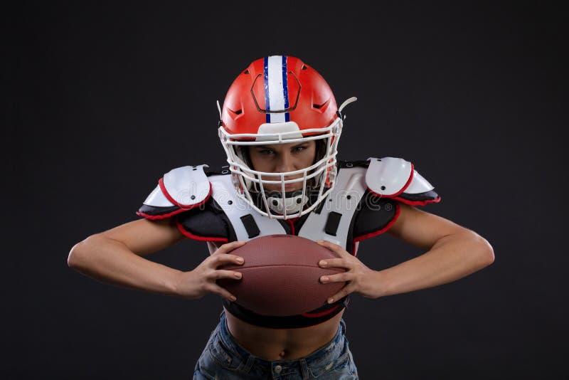 Mujer seria juguetona en el casco del jugador del rugbi que sostiene la bola y que grita agresivamente fotografía de archivo