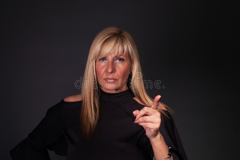 Mujer seria que aumenta su finger imagen de archivo libre de regalías