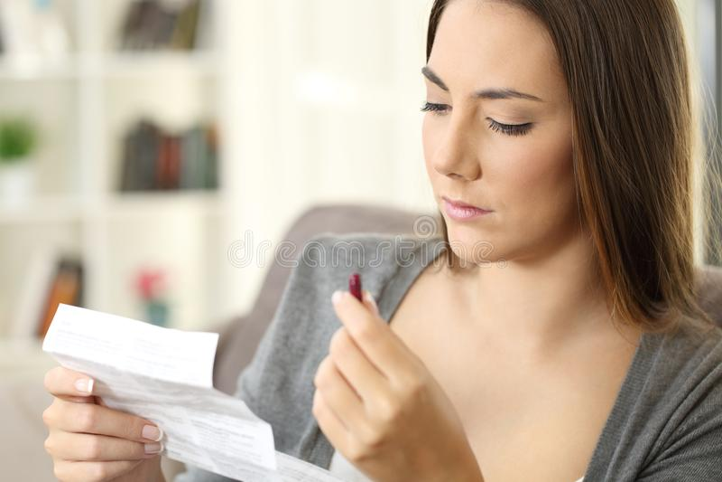 Mujer seria que lleva a cabo una medicina que lee un prospecto foto de archivo