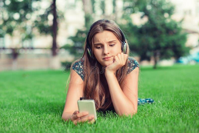 Mujer seria que manda un SMS en el teléfono descontentado agujereado preocupado con la conversación fotos de archivo