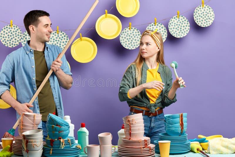 Mujer seria que mira al hombre sonriente mientras que trabaja en la cocina imagenes de archivo