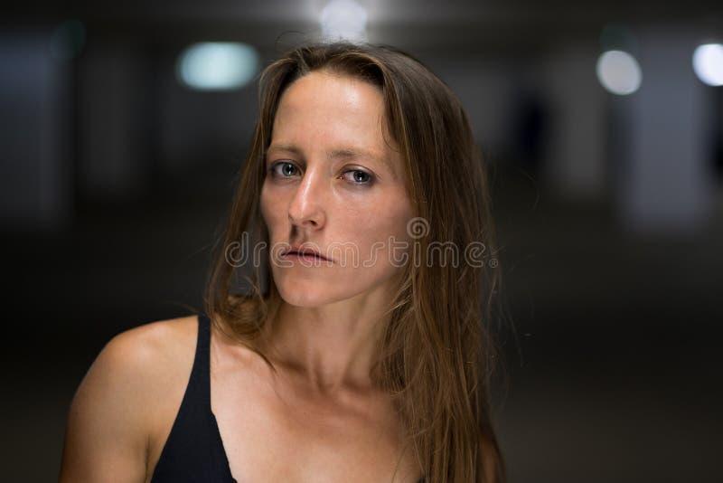 Mujer seria que mira especulativo la cámara foto de archivo