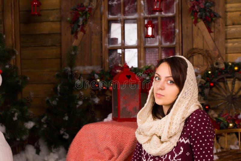 Mujer seria que pone la bufanda del invierno en la cabeza imagen de archivo