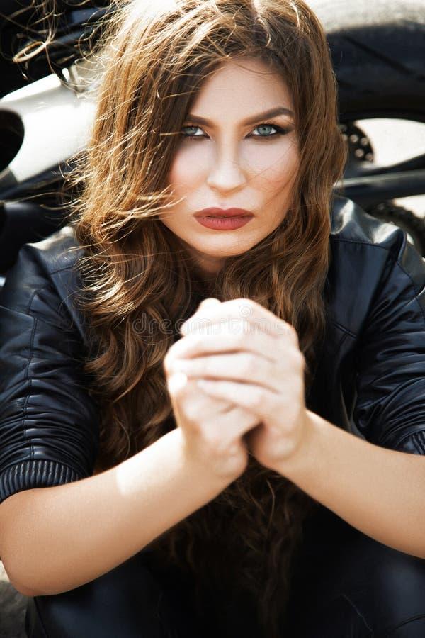Mujer sexual del motorista que lleva la chaqueta de cuero negra con su deporte m foto de archivo