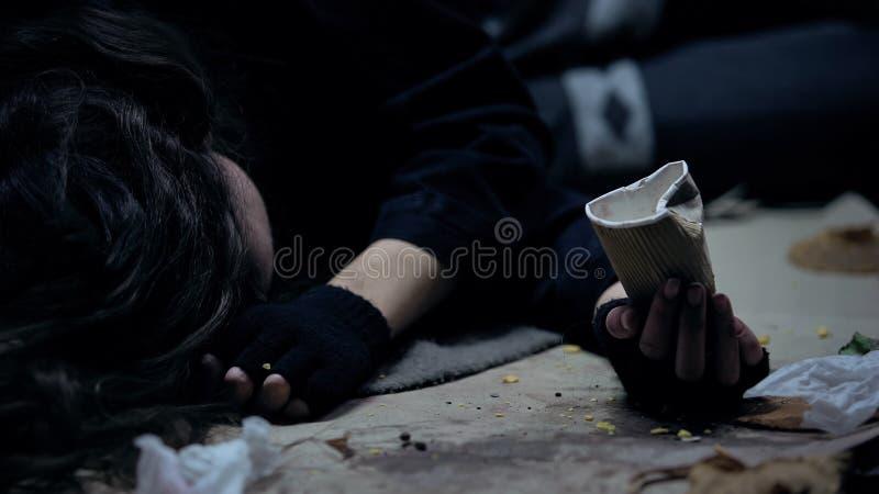 Mujer sin hogar con la taza de papel que miente en la tierra en el lugar sucio, pidiendo dinero fotos de archivo libres de regalías
