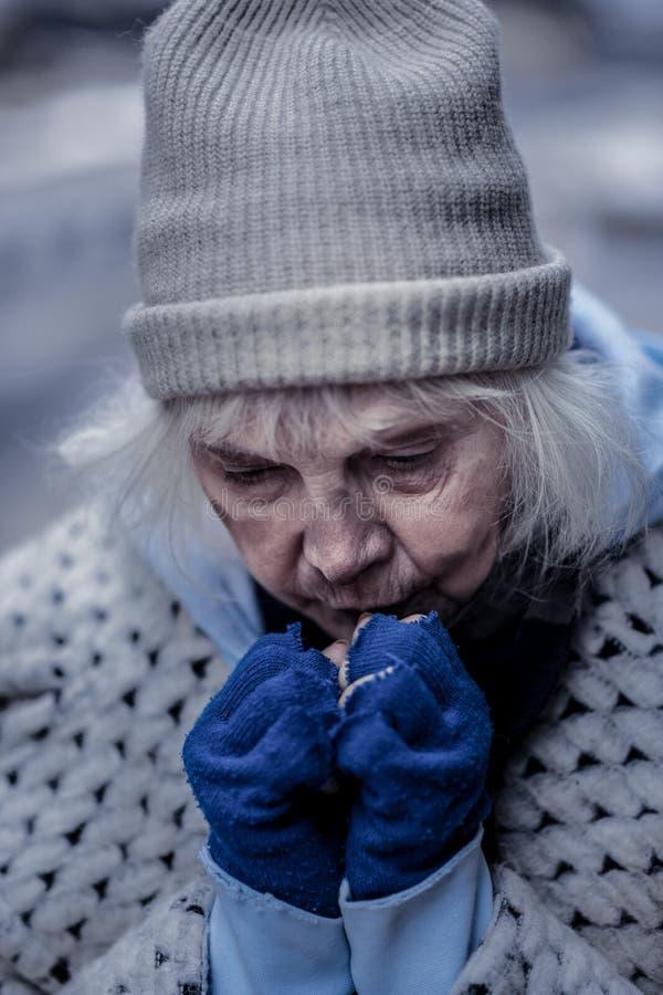 Mujer sin hogar deprimida que intenta calentarse las manos fotos de archivo