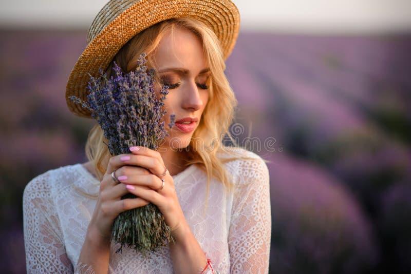 Mujer soñadora joven con el ramo en sus manos que se colocan en campo de florecimiento de la lavanda foto de archivo libre de regalías