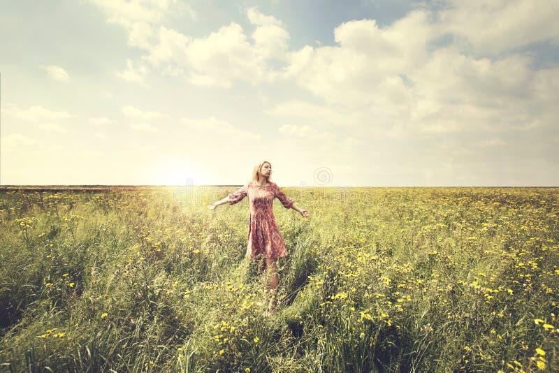 Mujer soñadora que camina en la naturaleza iluminada por el sol imagen de archivo libre de regalías