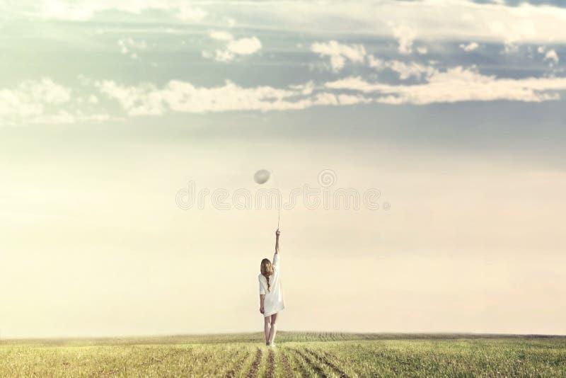 Mujer soñadora que camina hacia infinito con su globo blanco foto de archivo libre de regalías