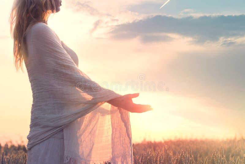 Mujer soñadora que sostiene el sol en sus manos fotos de archivo libres de regalías