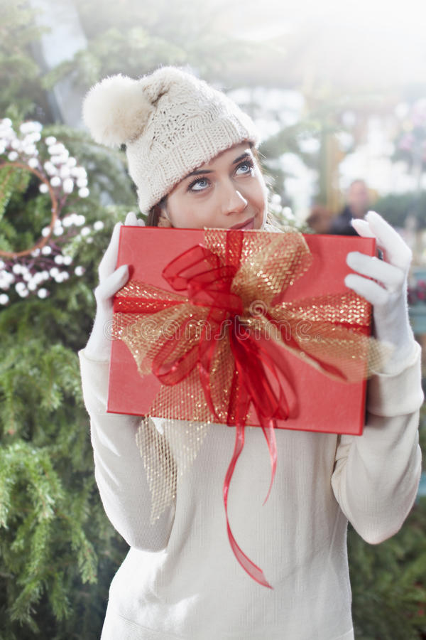 Mujer soñadora, sosteniendo su regalo de la Navidad foto de archivo libre de regalías