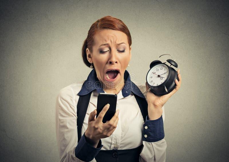 Mujer soñolienta con el teléfono móvil y el despertador imagen de archivo libre de regalías