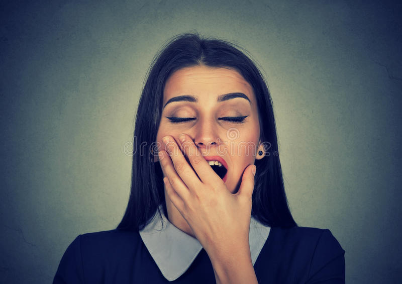 Mujer soñolienta con parecer de bostezo de la boca abierta de par en par agujereado fotografía de archivo