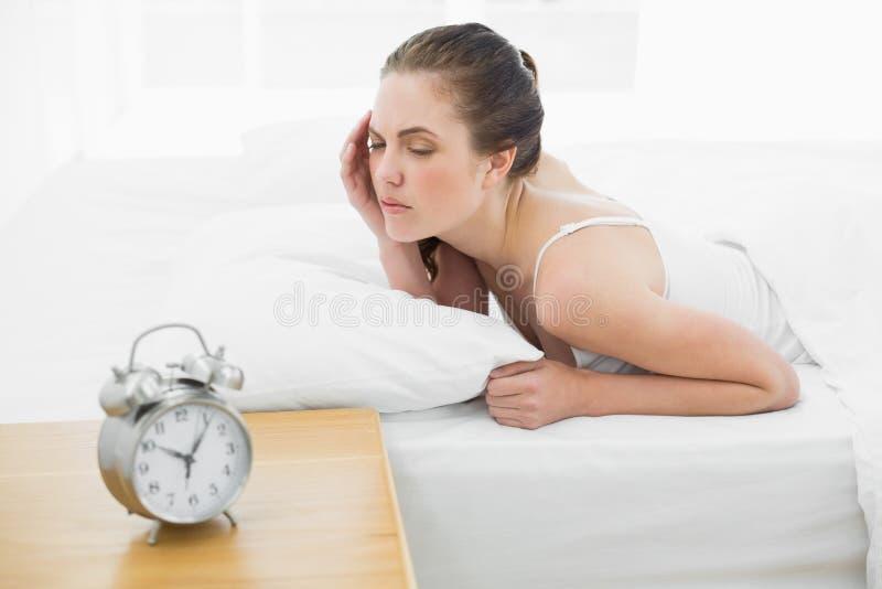 Mujer soñolienta en cama con el despertador en primero plano fotografía de archivo libre de regalías