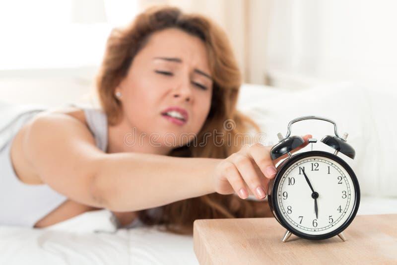 Mujer soñolienta joven que intenta apagar el despertador fotografía de archivo libre de regalías