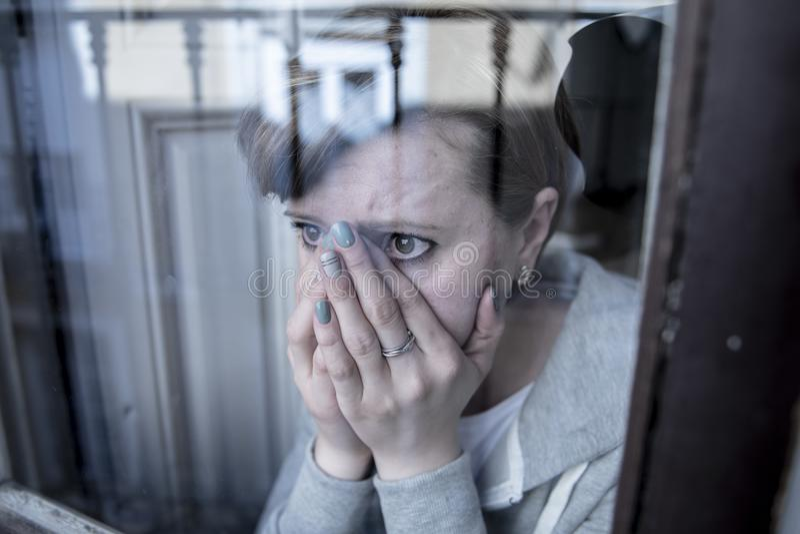 Mujer sola deprimida infeliz atractiva joven que mira la mirada triste a través de la ventana en casa imagenes de archivo