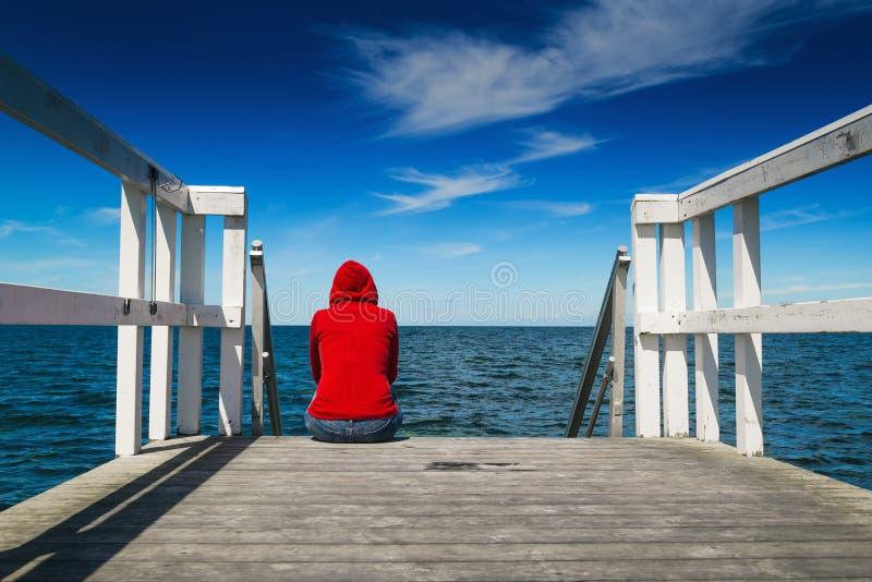 Mujer sola en camisa roja en el borde del embarcadero fotos de archivo libres de regalías