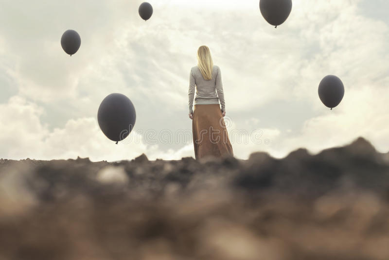 Mujer sola que camina hacia infinito en un lugar surrealista imagen de archivo libre de regalías