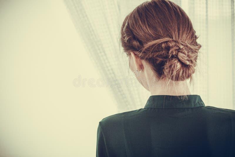 Mujer sola que mira con esperar de la ventana imagen de archivo libre de regalías