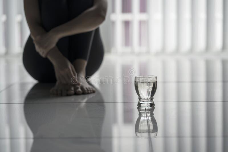 Mujer sola que se sienta con un vaso de agua fotografía de archivo