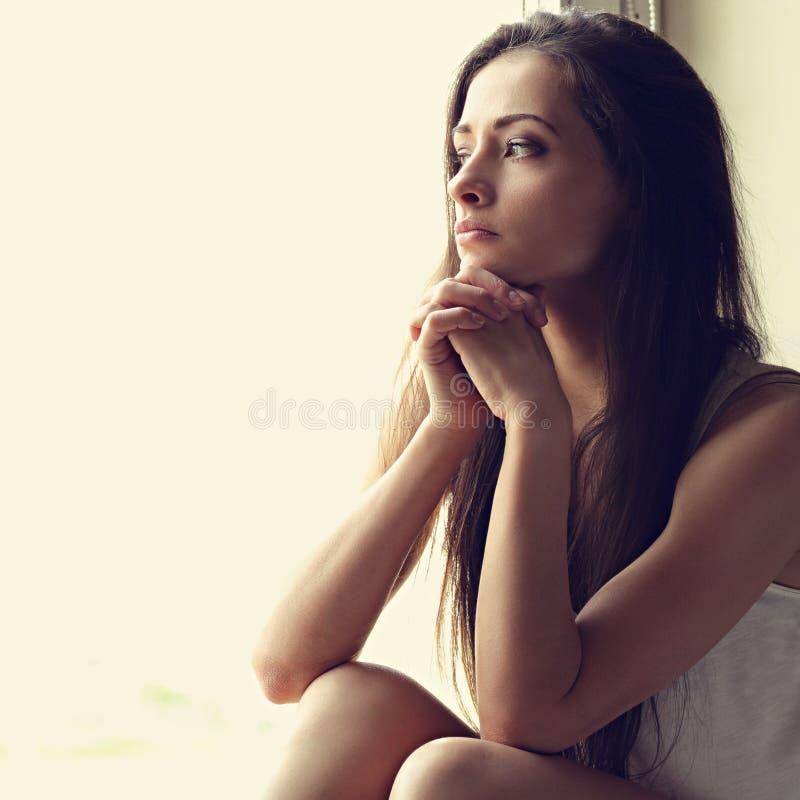 Mujer sola triste hermosa que se sienta y que piensa alrededor y lookin fotos de archivo libres de regalías