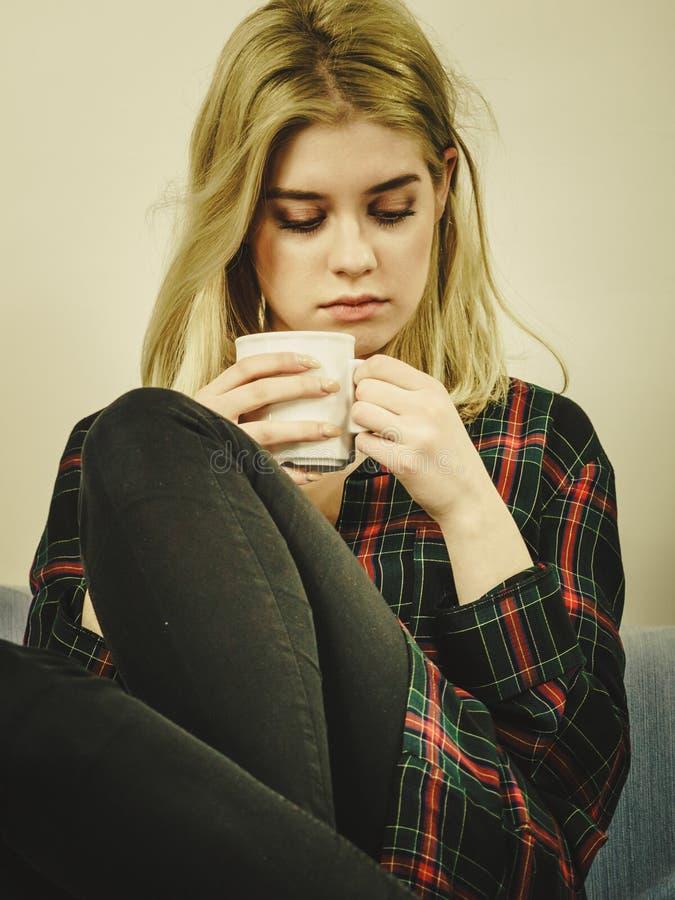Mujer sola triste que se sienta en el sof? con la taza imagenes de archivo