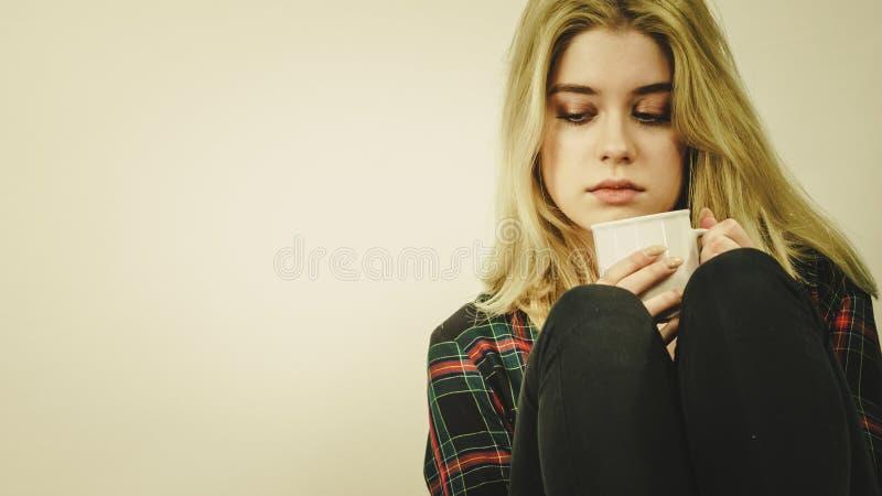 Mujer sola triste que se sienta en el sof? con la taza imagen de archivo libre de regalías
