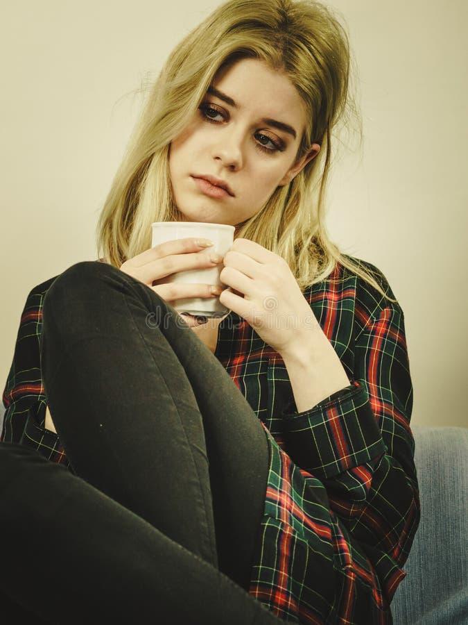 Mujer sola triste que se sienta en el sof? con la taza fotografía de archivo libre de regalías