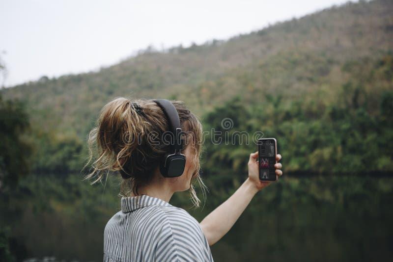 Mujer solamente en la naturaleza que escucha la música con los auriculares y smartphone imagen de archivo libre de regalías