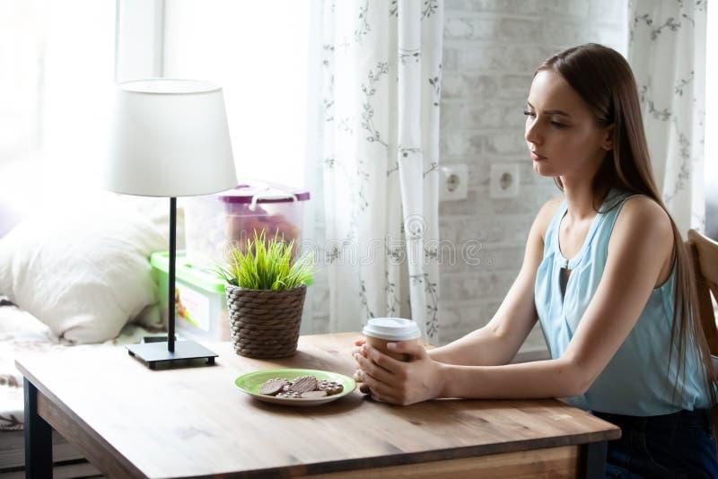 Mujer solamente joven que se sienta en la tabla y el café de consumición en café fotografía de archivo
