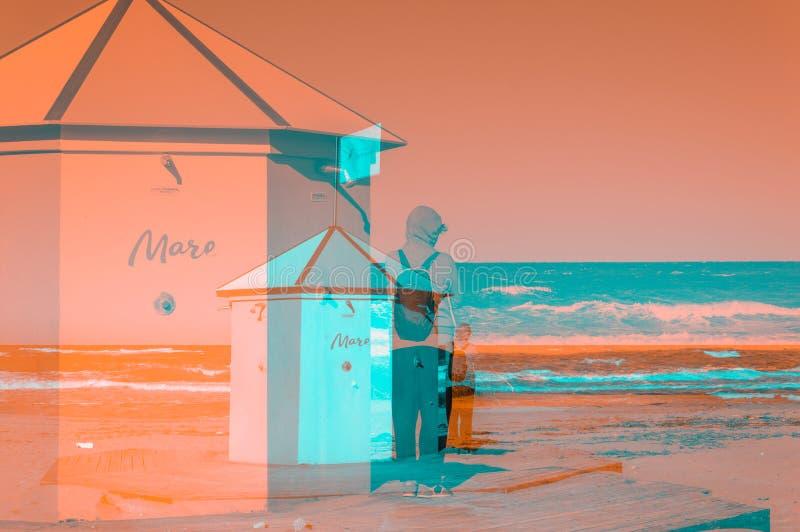Mujer solitaria cerca de una cabina de la ducha de la playa en la costa en un día ventoso de otoño fotos de archivo libres de regalías